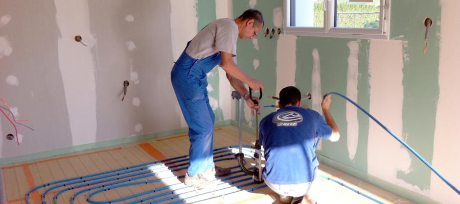 Plombiers installant le plancher chauffant